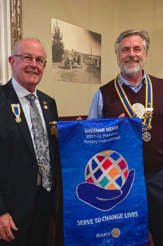 PDG Gary Roberts hands the 21-22 theme banner to President Chris Edwards
